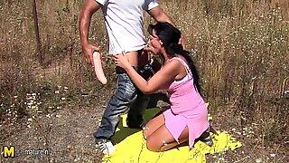 Horny amateur MILF fucking in an open field