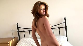 Fresh faced brunette poses naked in bed after stripping