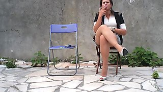 Nadejda smoke an cigarette on her chair ...